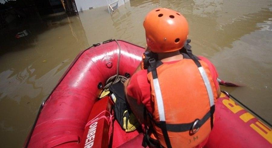 Imagem: Bombeiros usando botes para resgatar pessoas Bombeiros usam botes pra resgatar pessoas ilhadas pela chuva