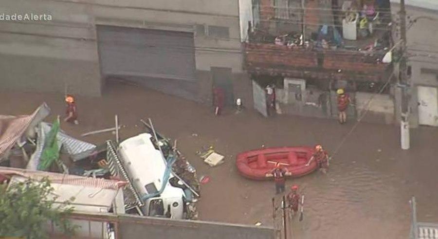 Imagem: Bombeiros usando botes Bombeiros usam botes pra resgatar pessoas ilhadas pela chuva
