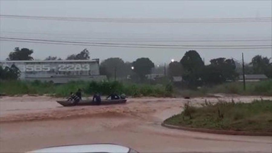 Imagem: Morador andando de barco na rua Ruas e casas ficam alagadas em município de MT após forte chuva