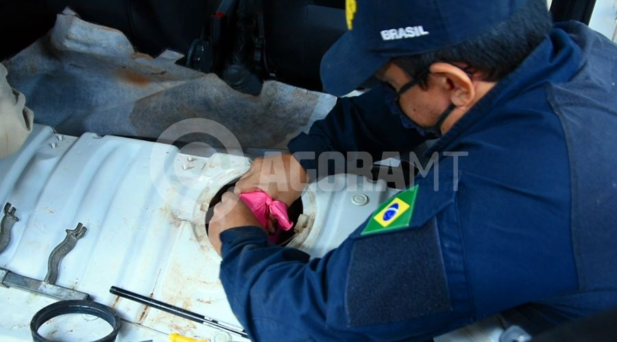 Imagem: Prf tirando a droga escondida do tanque de combustivel PRF encontra mais de 25kg de pasta base escondido em tanque de carro