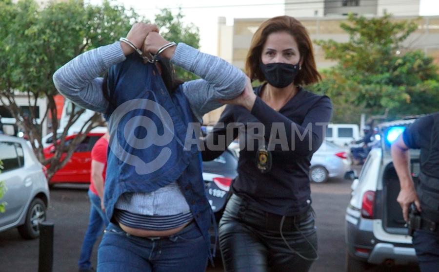 Imagem: Mulher sendo conduzida para a DP DHPP prende casal acusado de matar homem a tiros em 2019